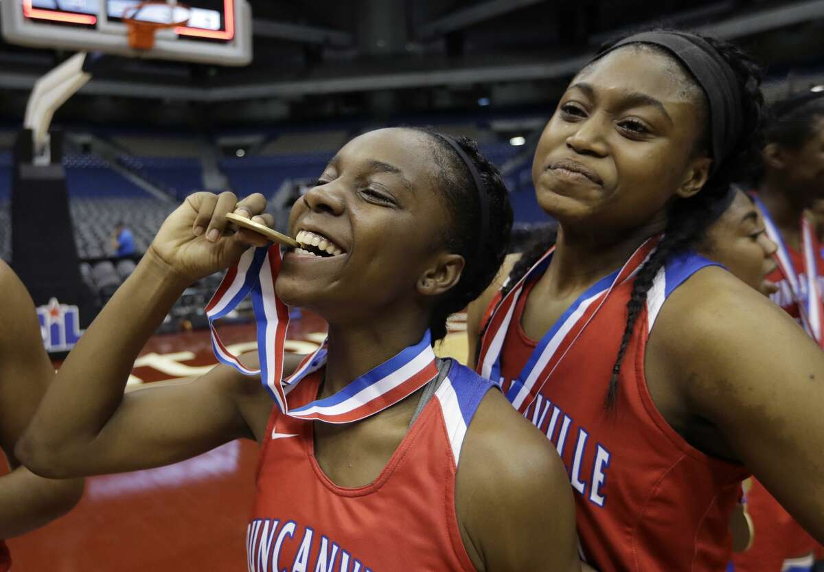Duncanville's Angel Flowers (11) bites her gold medal as she celebrates the team's win in the UIL Class 6A girls high school state final basketball game against Houston Cypress Ranch, Saturday, March 4, 2017, in San Antonio. (AP Photo/Eric Gay)