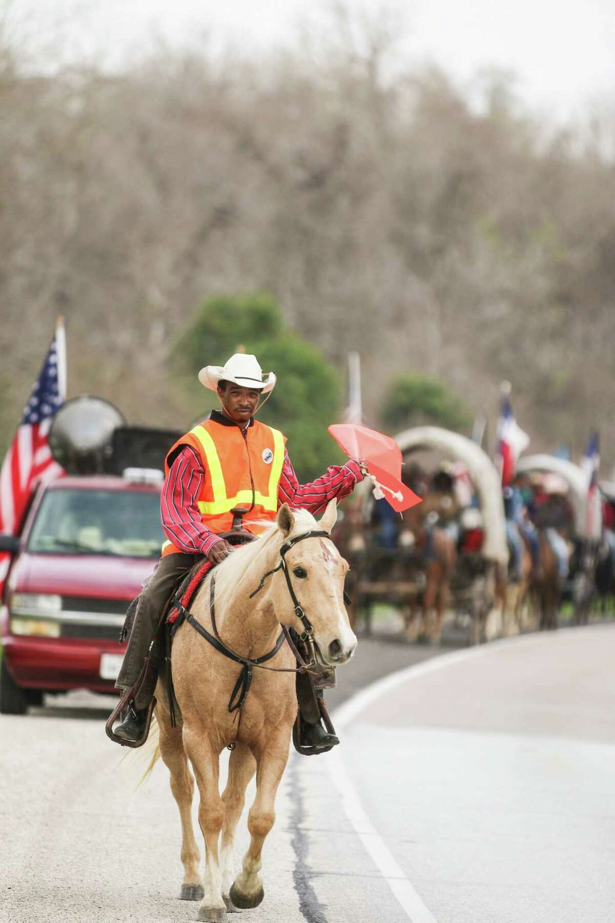 Scout Shannon Richards signals traffic away from the riders and wagons approaching as the Northeastern Trail Ride makes its way through the Dayton community on Feb. 28.