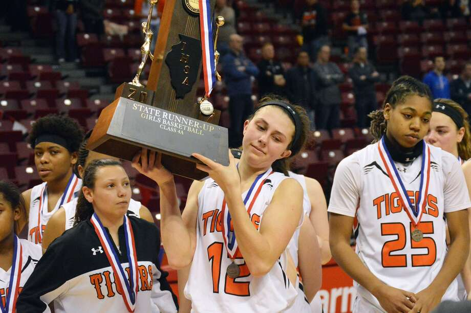 The Edwardsville Tigers accept the second-place trophy after falling to Geneva in the state championship game. Pictured from left are seniors Jasmine Bishop, Makenzie Silvey and Criste'on Waters.