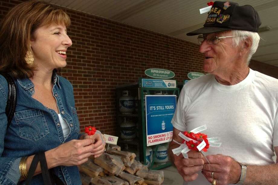 Megan Scully, of Fairfield, speaks with Korean War veteran Joe Konkol after she bought a handmade poppy in front of Super Stop and Shop, on Kings Highway Cutoff, in Fairfield, Conn. Friday, May 28th, 2010. The poppies are made by disabled veterans, and are sold by a number of veteran's organizatons to raise money and awareness for disabled veterans. Konkol is a member of the Lt. Raymond J. Bower Post 1466 of the Catholic War Veterans, in Bridgeport. Photo: Ned Gerard / Connecticut Post