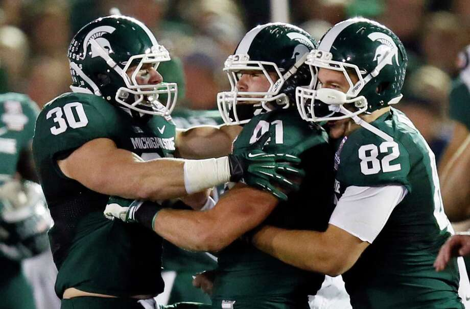 Michigan State's Riley Bullough, left, moved from fullback to linebacker during his college career. He is trying to follow the footsteps of three family members, including current Texans player and brother Max Bullough to the NFL. Photo: Danny Moloshok, Associated Press / FR161655 AP