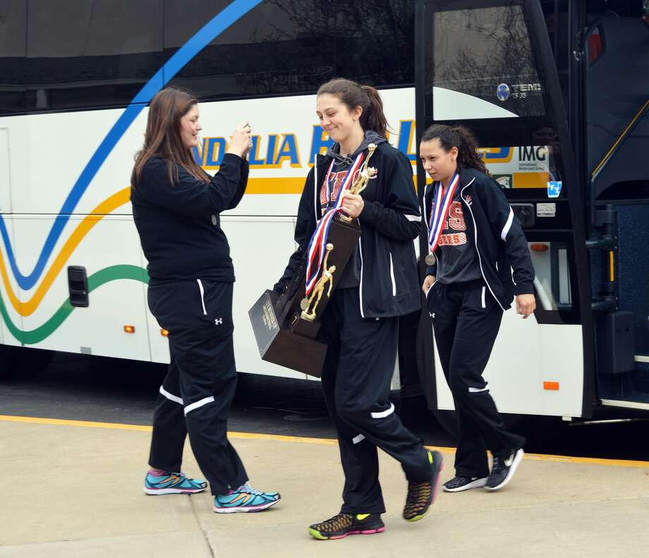 Edwardsville seniors Makenzie Silvey, center, and Jasmine Bishop walk off the bus with the second-place trophy on Sunday.