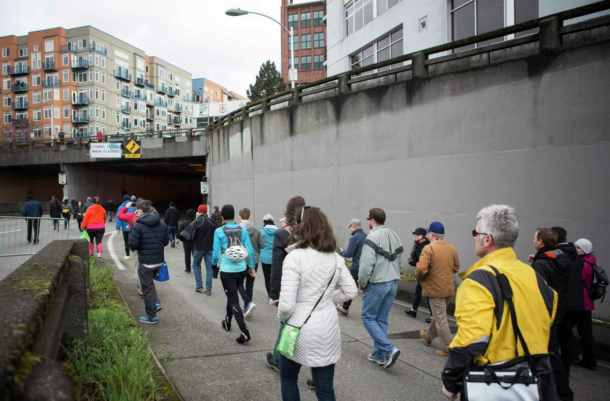People stream into the northbound lanes of the Battery Street Tunnel during Walk the Battery, which allowed the general public to explore the tunnel on Sunday, Mar. 5, 2017. The walk was part of an ongoing art initiative,