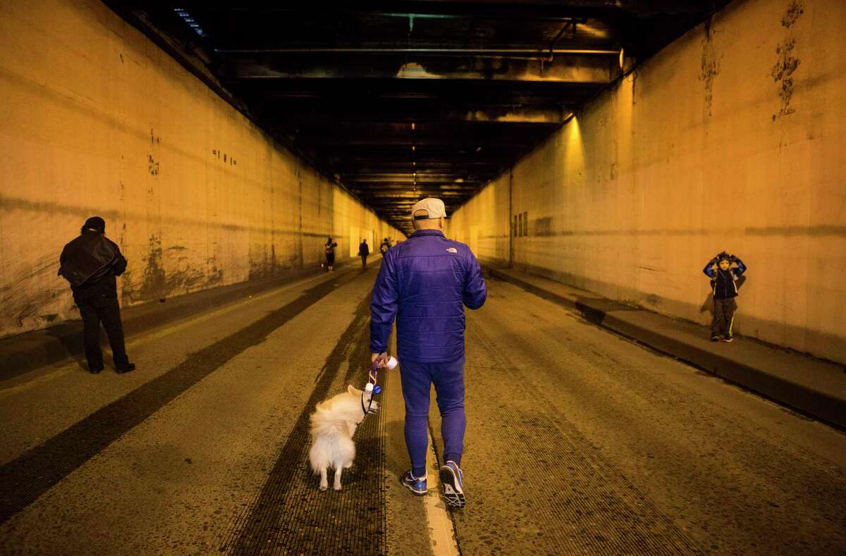 Leland Yu of Seattle walks down the tunnel with Yugi, an American Eskimo, during Walk the Battery, which temporarily opened the Battery Street Tunnel to the general public to explore on Sunday, Mar. 5, 2017. The walk was part of an ongoing art initiative,