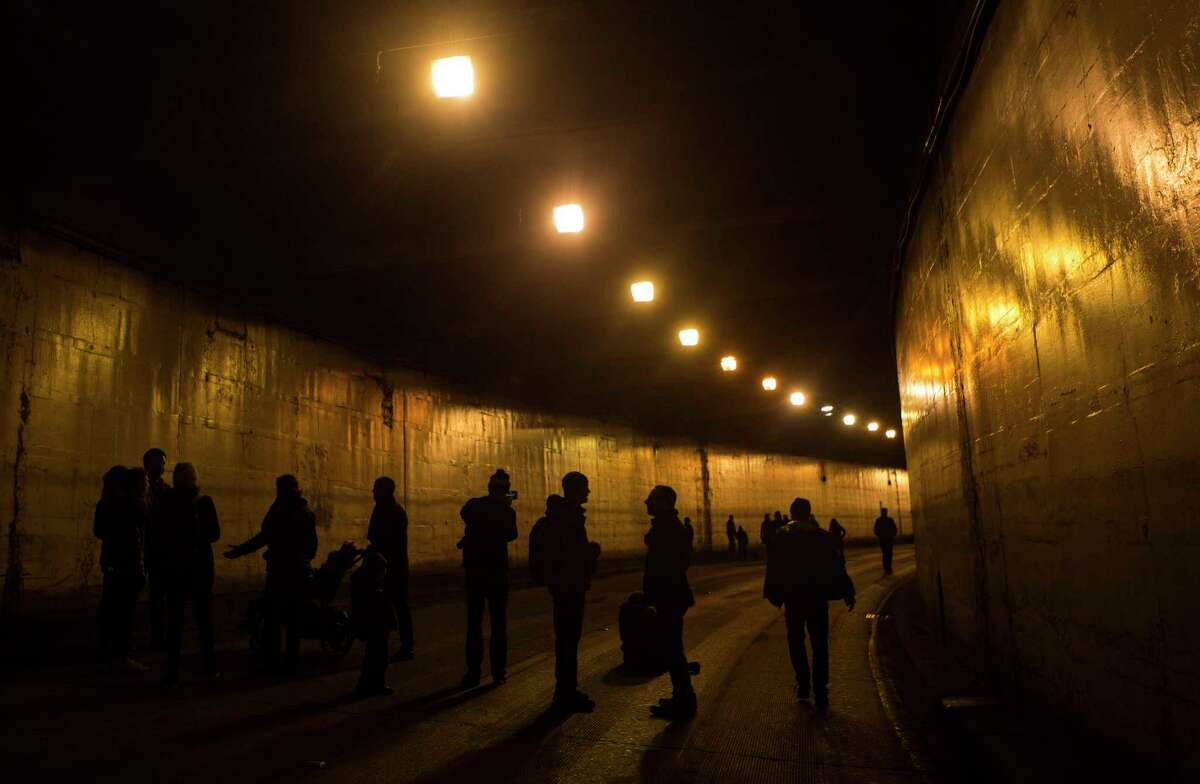 People are silhouetted against the dim lights of the northbound Battery Street Tunnel lanes during the Walk the Battery event on Sunday, Mar. 5, 2017. The walk was part of an ongoing art initiative,