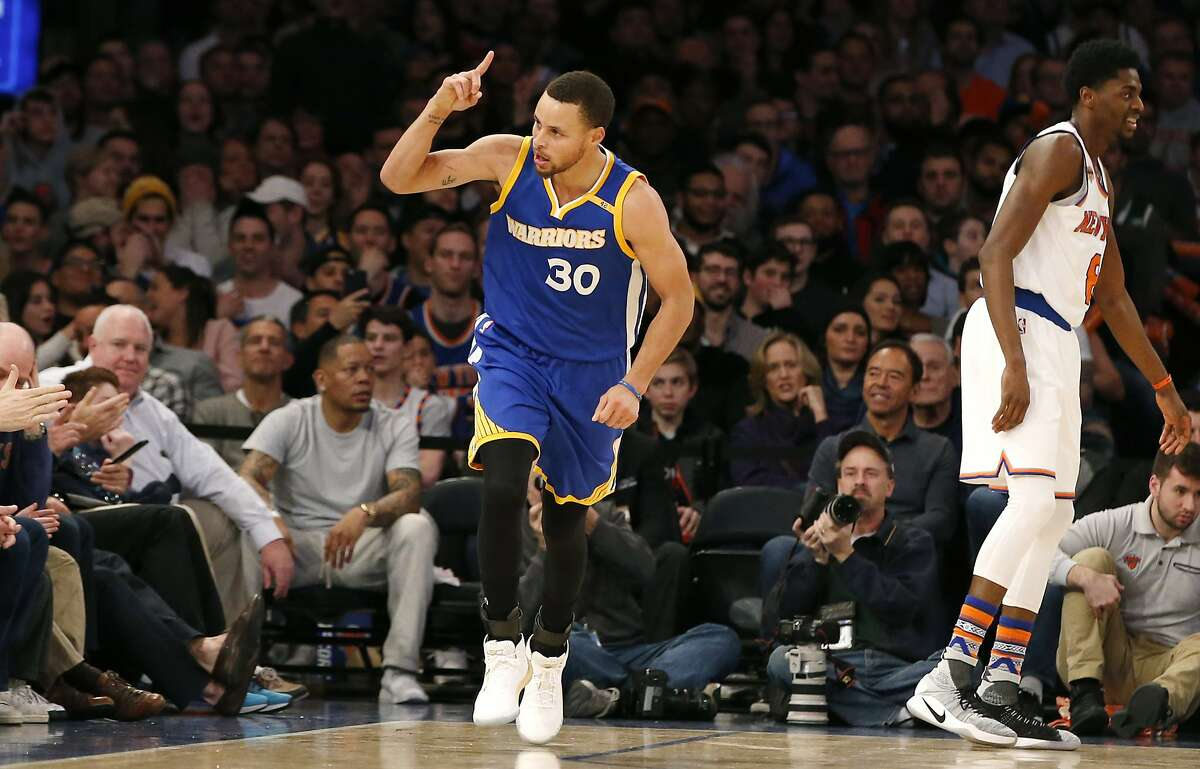 Golden State Warriors guard Stephen Curry (30) reacts after sinking a three-point shot as New York Knicks guard Justin Holiday (8) walks away in the second half of an NBA basketball game at Madison Square Garden in New York, Sunday, March 5, 2017. Curry had 31 points as he led the Warriors to a 112-105 defeat of New York Knicks 112-105. (AP Photo/Kathy Willens)
