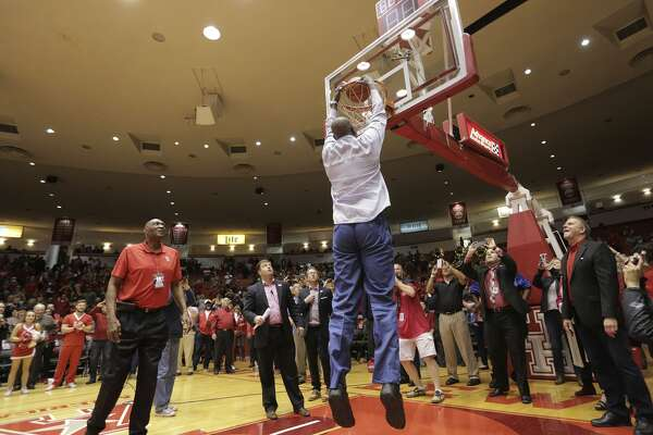 Houston Cougars alumni Hakeem Olajuwon dunks the a basketball that will be used in the first game next season at the new arena in a post-game ceremony at Hofheinz Pavilion on Sunday, March 5, 2017, in Houston. Houston won the game 73-51.( Elizabeth Conley / Houston Chronicle )