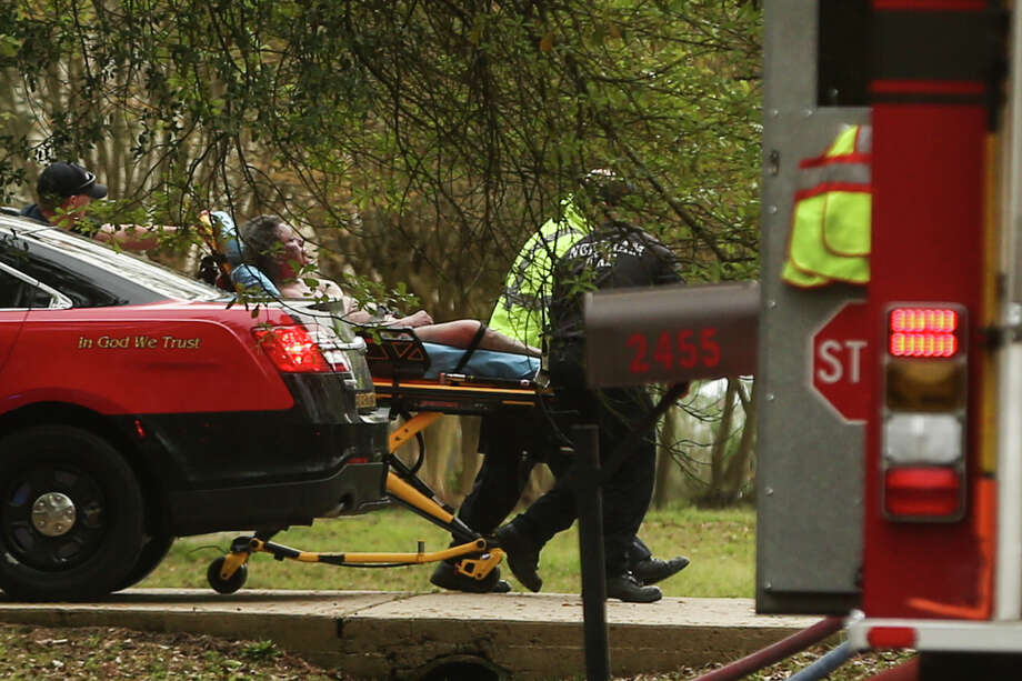 A victim from the house fire on Sunday, March 5, 2017, on Ripplewood Drive is transported to an ambulance by firefighters and paramedics. Photo: Michael Minasi, Staff Photographer / © 2017 Houston Chronicle