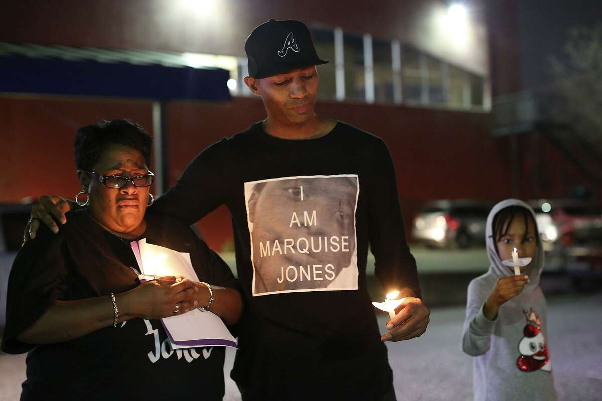 Mike Lowe, of SATX4, with his daughter, Naomi Lowe, 9, puts his arm around Debbie Bush, the aunt of Marquise Jones, after Lowe addressed the crowd gathered for the vigil for the third anniversary of Jones' death outside Chacho's restaurant in San Antonio on Tuesday, Feb. 28, 2017.