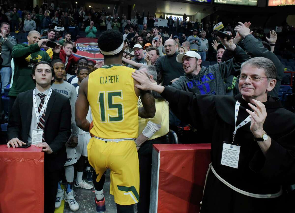 Siena College President Br. F. Edward Coughlin, right, congratulates Nico Clareth of Siena as he makes his way to the locker room after helping his team beat Monmouth in their semifinal MAAC Basketball Tournament game at the Times Union Center on Sunday, March 5, 2017, in Albany, N.Y.