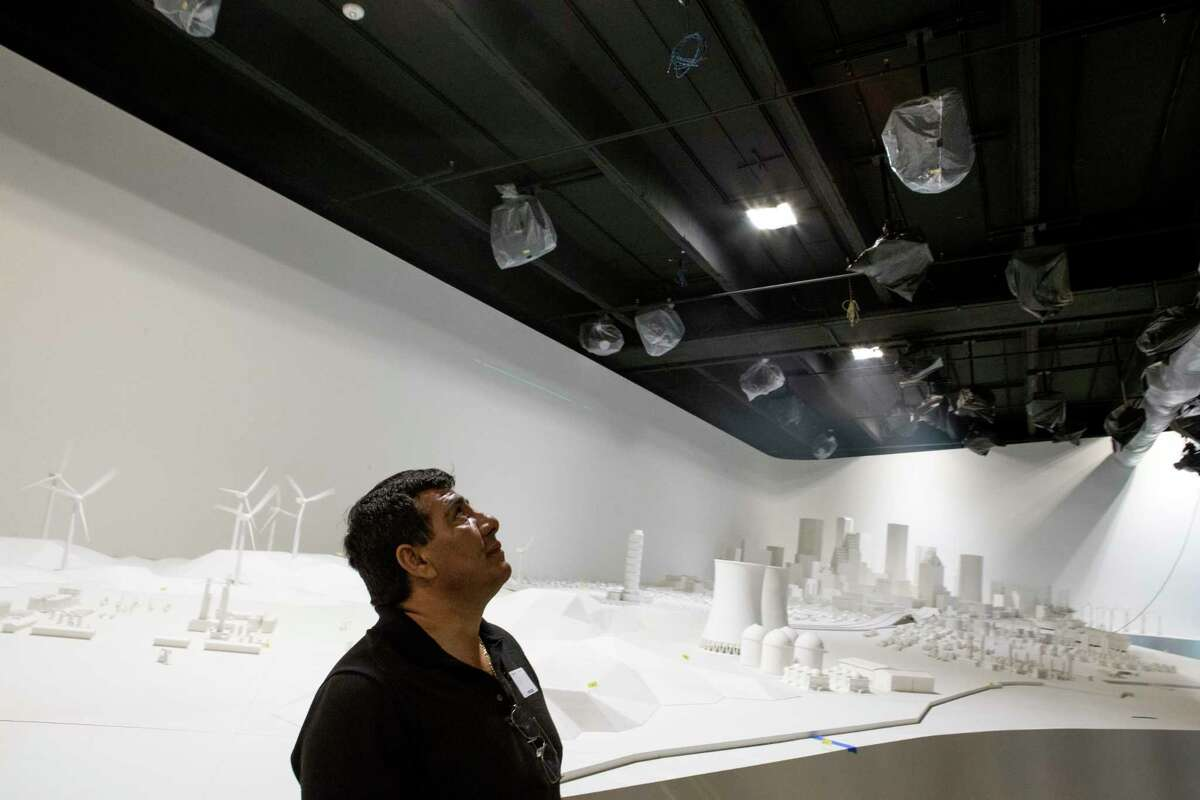 """Esteban Gonzalez examines the 2,500-square-foot """"Energy City"""" exhibit in the new Wiess Energy Hall. Once completed, the model landscape will represent Houston, the Gulf coastal water and part of southeast Texas and will be illuminated by a series of projectors."""