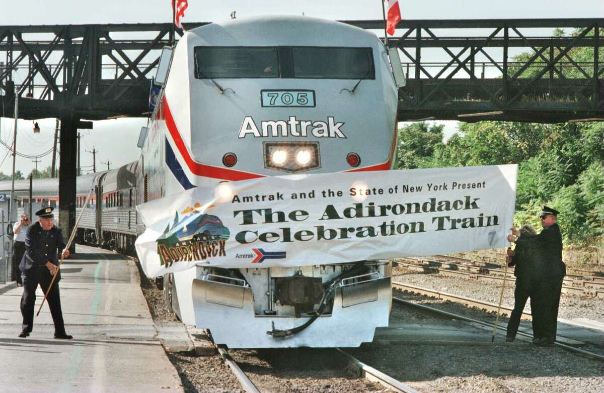 Times Union photo by LUANNE M. FERRIS -- RENSSELAER, FRIDAY, SEPT. 20, 1996. AMTRAK CELEBRATES THE RETURN OF THE 'ADIRONDACK' TODAY. THE TRAIN WILL FOLLOW THE NORTHBOUND ROUTE OF THE SERVICE FROM NEW YORK CITY TO MONTREAL. HERE THE TRAIN IS REINTRODUCED TO THE PUBLIC AS IT BREAKS THE BANNER ON THE TRACKS AT THE RENSSLEAR STATION. 09/21/96
