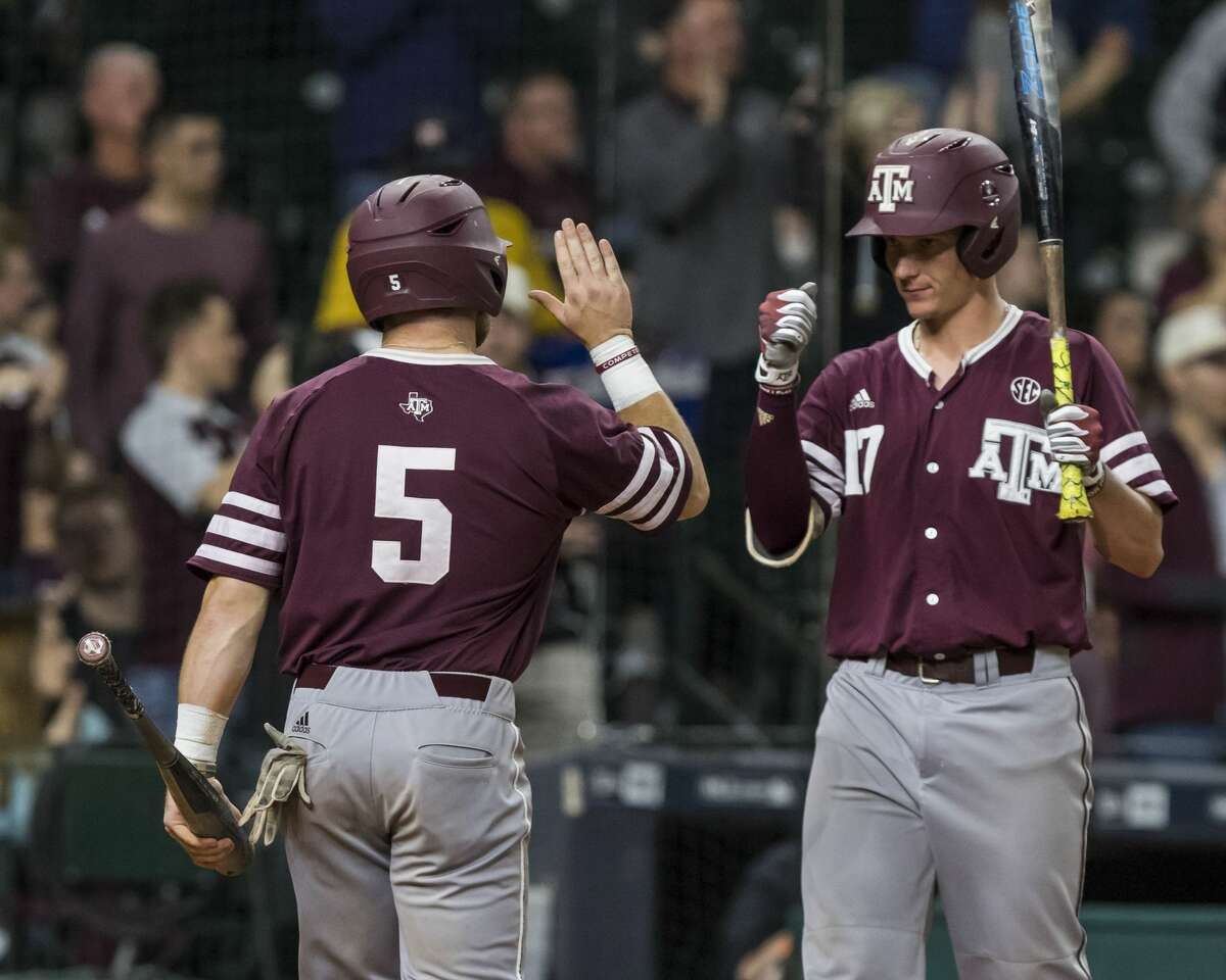 Texas A&M 's Logn Foster (5) Joel Davis (17) celebrate after Foster scored during a NCAA baseball game at Minute Maid Park on Sunday, Mar. 5, 2017, in Houston. (Joe Buvid / For the Houston Chronicle)
