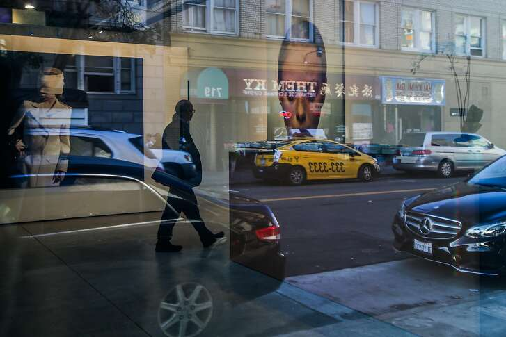 Ellis Street is reflected in the windows of Modernism gallery where paintings can be seen hung up on the walls in San Francisco, California, on Thursday, Feb. 23, 2017.