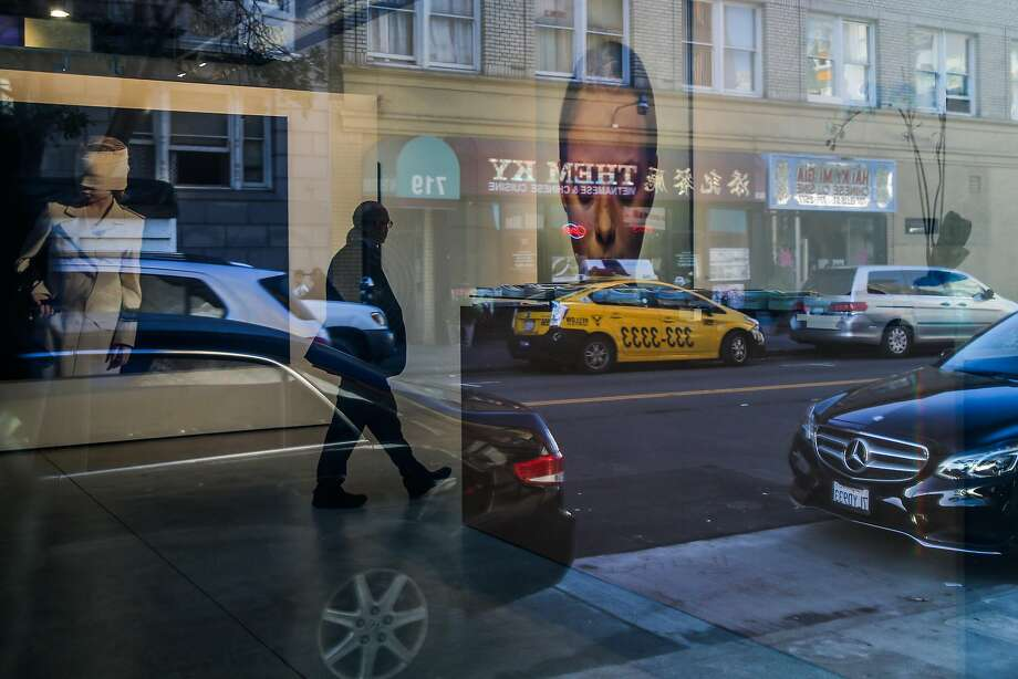 Ellis Street is reflected in the windows of Modernism gallery, where Gottfried Helnwein paintings can be seen on the walls. Photo: Gabrielle Lurie, The Chronicle