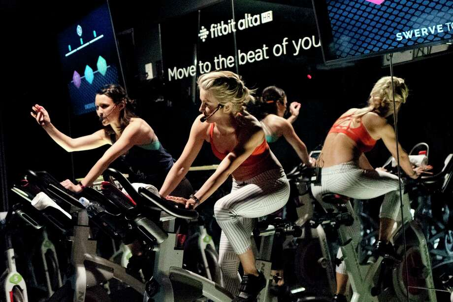 In this March 1, 2017 photo, Jamey Powell, left, and Julianne Hough lead an exercise class as the participants are introduced to the Alta HR fitness tracker at Swerve cycling center in New York. Fitbit is the leading seller of wearable devices, but it's facing a steep decline because most of its sales are in the U.S., where many people who want a fitness tracker already have one. Photo: Mark Lennihan, AP / Copyright 2017 The Associated Press. All rights reserved.