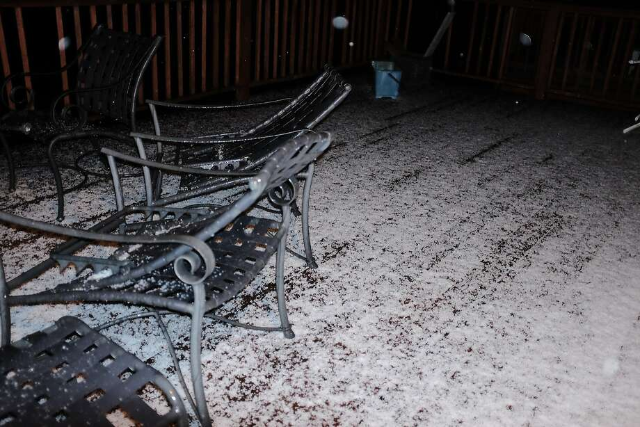 A brief hailstorm Sunday night in Pacifica leaves a homeowner's deck covered with ice pellets. Photo: Mike Moffitt/SFGATE
