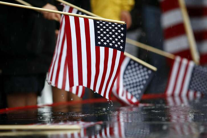 Fans hold American flags in the rain during the dock out show before the start of race 14 of the America's Cup Finals in San Francisco, CA Saturday September 21, 2013.