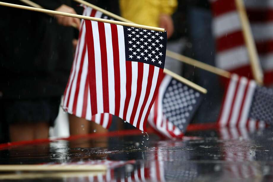 Fans hold American flags in the rain during the dock out show before the start of race 14 of the America's Cup Finals in San Francisco, CA Saturday September 21, 2013. Photo: Michael Short, The Chronicle