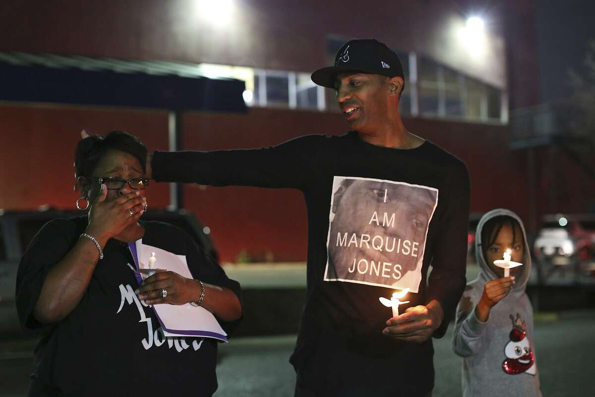 Mike Lowe, of SATX4, with his daughter, Naomi Lowe, 9, puts his arm around Debbie Bush, the aunt of Marquise Jones, after Lowe addressed the crowd gathered for the vigil on Feb. 28, 2017, for the third anniversary of Jones' death.