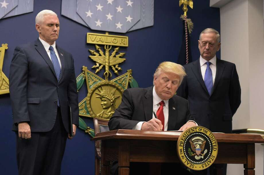 """(FILES) This file photo taken on January 27, 2017 shows  US President Donald Trump signing an executive order alongside US Defense Secretary James Mattis and US Vice President Muike Pence at the Pentagon in Washington, DC. Trump signed an order Friday to begin what he called a """"great rebuilding"""" of the US armed services.  The White House said on February 26, 2017, US President Donald Trump wants to hike defense spending by $54 billion, with offsetting cuts in foreign assistance and other non-military spending. Trump is expected to address budget items on February 28 during his addess to a joint session of congress.  / AFP PHOTO / MANDEL NGANMANDEL NGAN/AFP/Getty Images Photo: MANDEL NGAN, Staff / AFP/Getty Images / AFP or licensors"""