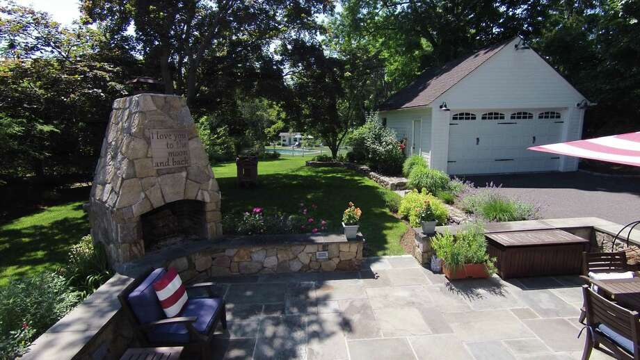Many improvements were made to the property as well as the house. The backyard includes an in-ground swimming pool at the far end and closer to the house is a bluestone patio with an outdoor fireplace and stone sitting wall.