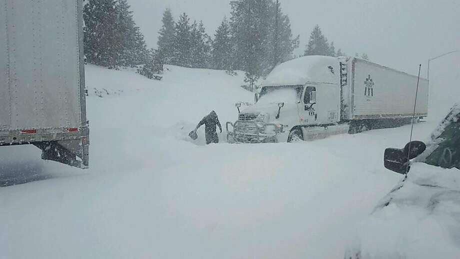 A man uses a bucket to dig out a truck in Donner Pass after heavy snowfall Sunday. Photo: California Highway Patrol