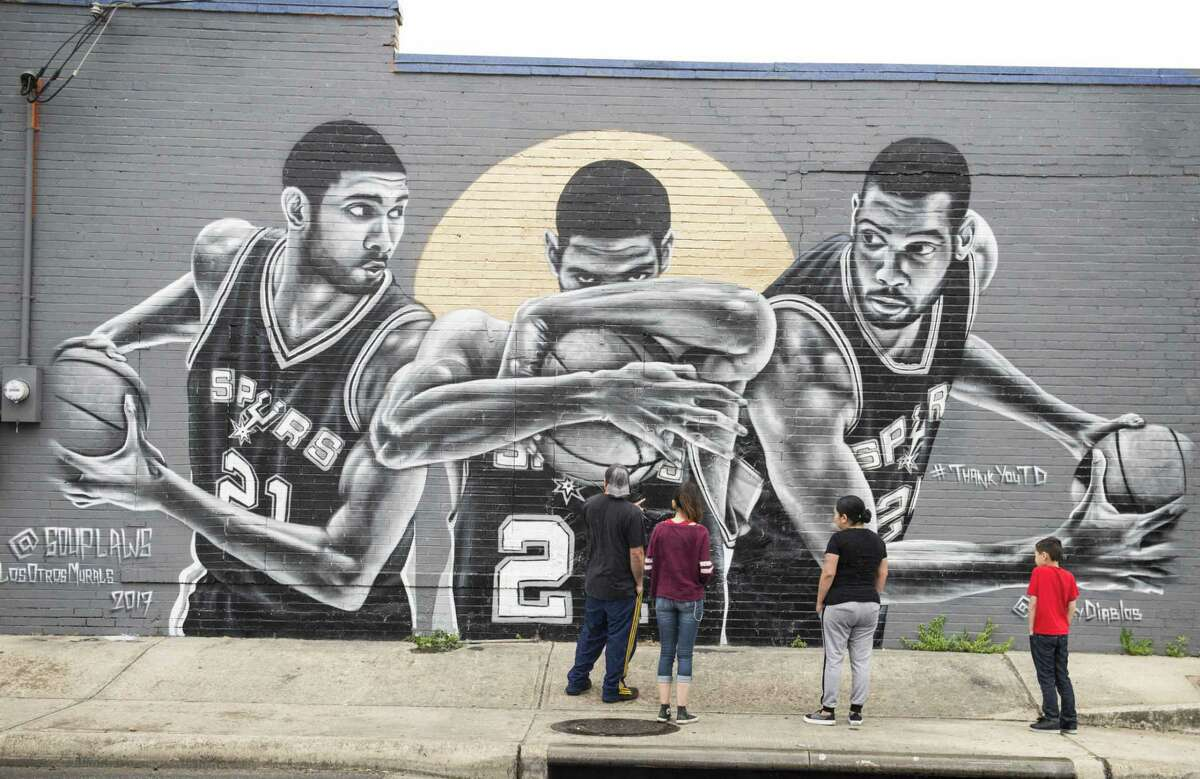 A group of children check out Nik Soup's mural dedicated to the Spurs at Franky Diablo's.