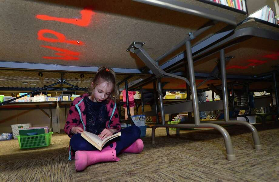 Fiona Ellis, 7, finds a quiet place to read during the 25th annual Westport Library Almost Spring book sale Saturday, March 4, 2017, in Westport, Conn. Photo: Erik Trautmann / Hearst Connecticut Media / Norwalk Hour