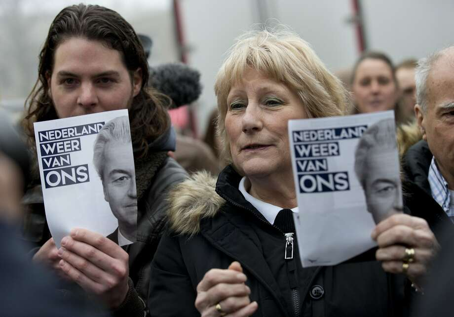"Supporters of far-right candidate Geert Wilders hold flyers bearing his portrait at a campaign rally in Spijkenisse, Netherlands, last month. The language reads: ""Netherlands ours again."" Photo: Peter Dejong, Associated Press"