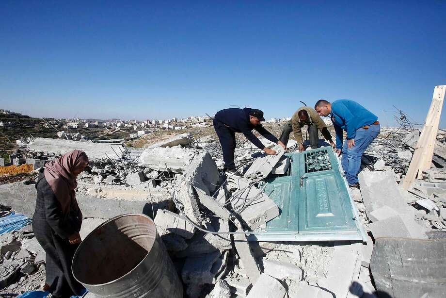 Palestinians help clear the debris of a home after it was demolished, by Israeli bulldozers bulldozers as they were reportedly built illegally without a permit, near the West Bank town of Hebron on March 6, 2017. / AFP PHOTO / HAZEM BADERHAZEM BADER/AFP/Getty Images Photo: HAZEM BADER, AFP/Getty Images