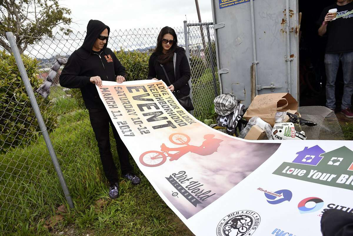 AC Thompson, left, and Jasmin Malabed unfurl a new banner at Dirt World in Richmond, CA, on Saturday March 4, 2017. Dirt World is a bike skills park currently under development in Richmond, CA and is the brainchild of Richmond residents Jasmin Malabed and Dennis �D2� Hoskins, founders of the Dope Sauce Bike Club, a grassroots program that introduces city kids to cycling of all varieties.