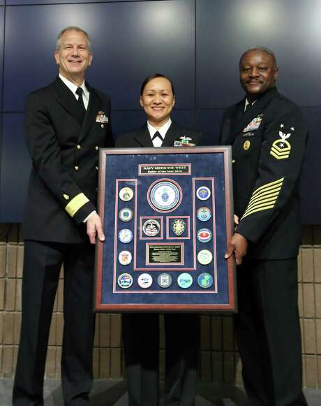 Rear Adm. Paul Pearigen, Commander Navy Medicine West (left), and Master Chief Hosea Smith, Command Master Chief, Navy Medicine West (right), present the Navy Medicine West Sailor of the Year plaque to Petty Officer 1st Class Tiffany Kidd, from U.S. Naval Hospital Yokosuka, in an auditorium packed with Sailors and civilians at Navy Medicine West Headquarters. (Photo by Chief Petty Officer Kimberley Blaine-Sweet /Released) Photo: Navy Public Affairs /