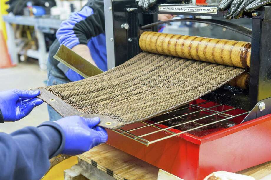 """Argonne researchers wring out an """"Oleo Sponge"""" pad to extract crude oil absorbed during tests at a seawater tank facility in Leonardo, N.J. Both the oil and the pad can be reused after this process. Photo: Argonne National Laboratory / Argonne National Laboratory"""