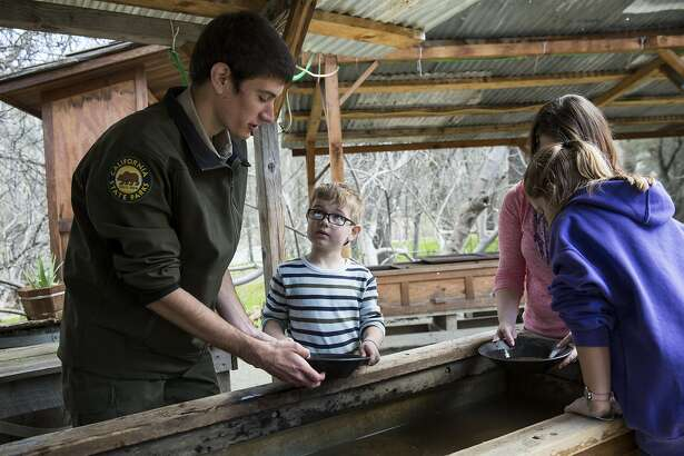 Stuart Kelly, a season park aide, helps six-year-old Ryan Sherman, Jennifer Sherman and and nine-year-old Emma Sherman (left to right) pan for gold at the Marshall Gold Discovery State Historic Park in Coloma, Calif., on Saturday, March 4, 2017. The park encompasses most of the historic town of Coloma where gold was found by James Marshall in 1848.