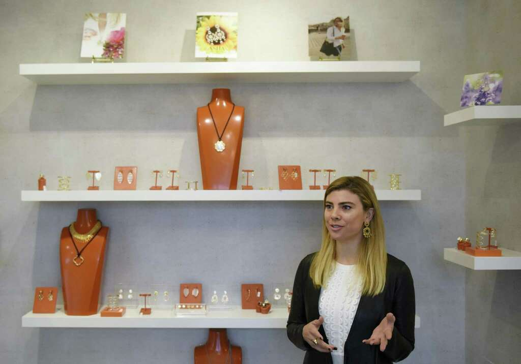 Asha designer and owner Ashley McCormick shows items from her collection at the Asha jewelry and accessory store in Greenwich on March 1. Asha recently opened on Greenwich Avenue, offering jewelry and accessories inspired by art, architecture and world travel. Photo: Tyler Sizemore / Hearst Connecticut Media / Greenwich Time