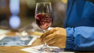 A visitor to Ironstone Vineyards swirls a glass of wine while wine tasting at the winery's tasting room in Murphys, Calif, on Sunday, February 19, 2017.