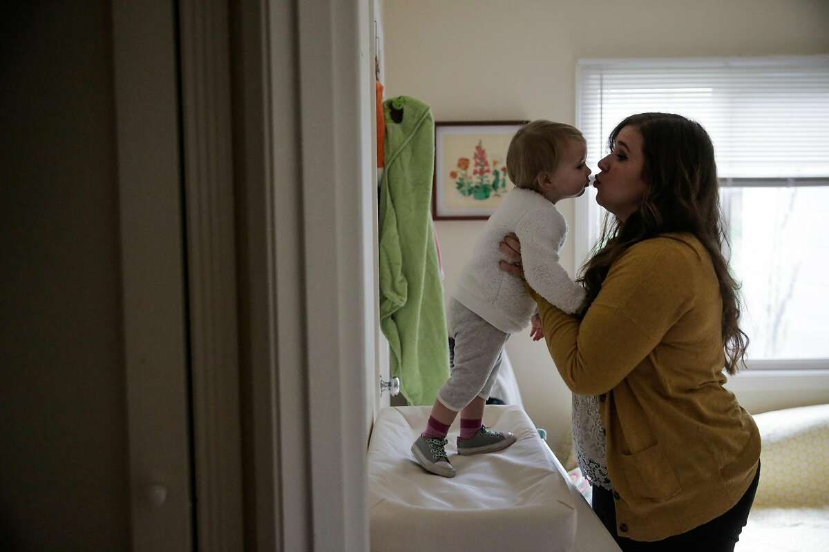 Ashley Summers kisses daughter Alice Paulson while getting her dressed. Summers is an aide to Supervisor Katy Tang, who will propose the new law about pumping milk in workplaces.