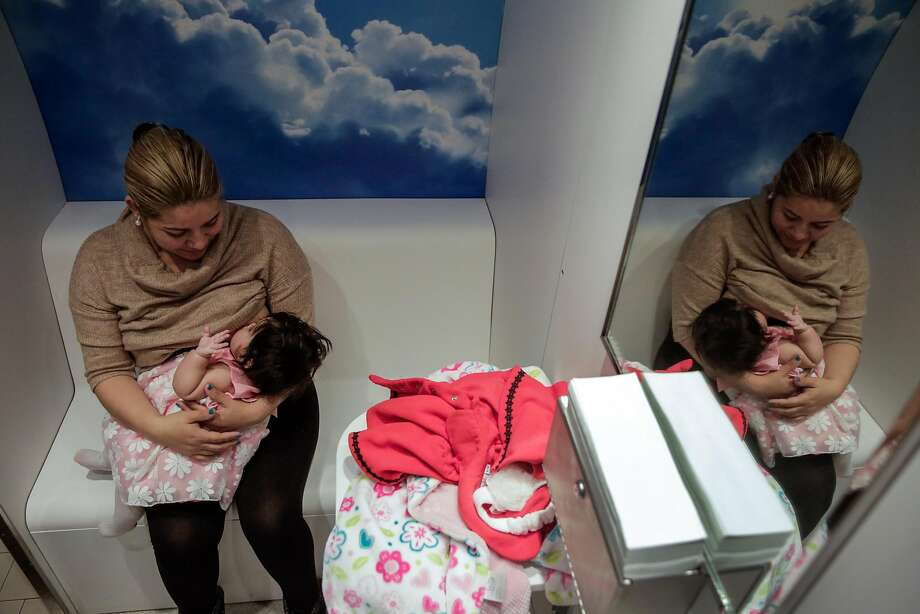 Mavet Coronel feeds her 6-month-old daughter, Allison, in the lactation pod at San Francisco City Hall. A proposal by Supervisor Katy Tang would require workplaces to provide space for pumping milk. Photo: Gabrielle Lurie, The Chronicle