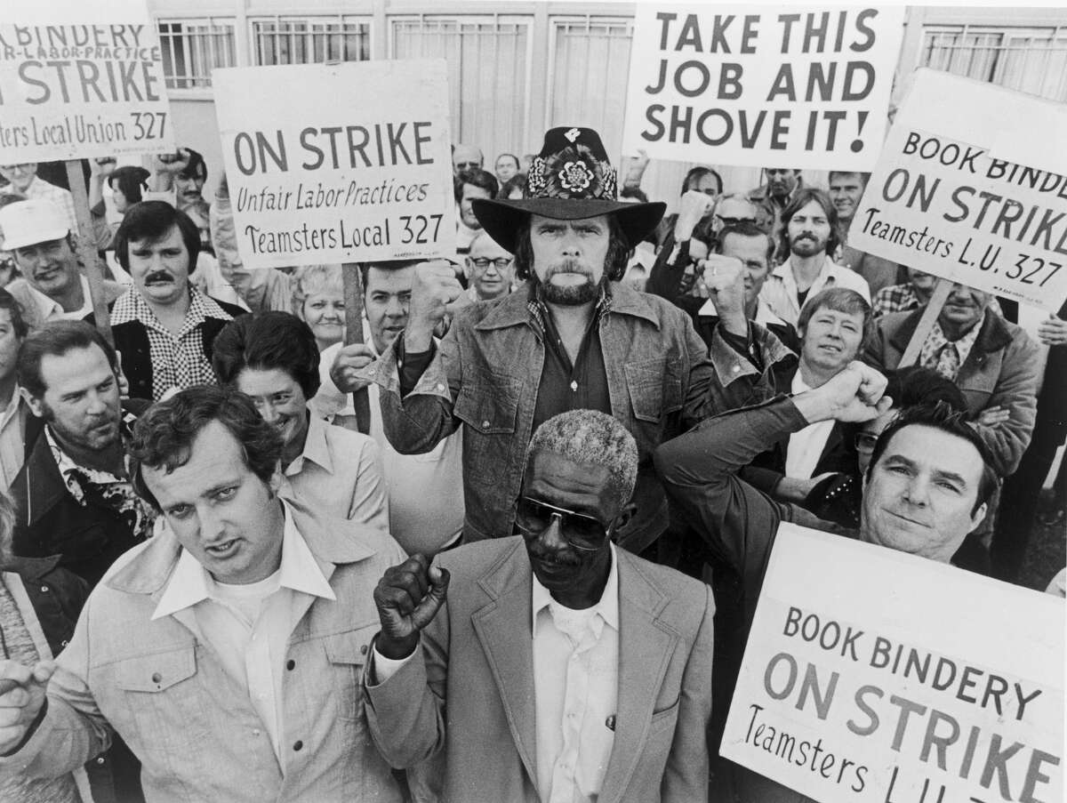 American country singer and songwriter Johnny Paycheck holds a teamsters union sign while joining a group of striking bookbinders, 1977. (Photo by Hulton Archive/Getty Images)