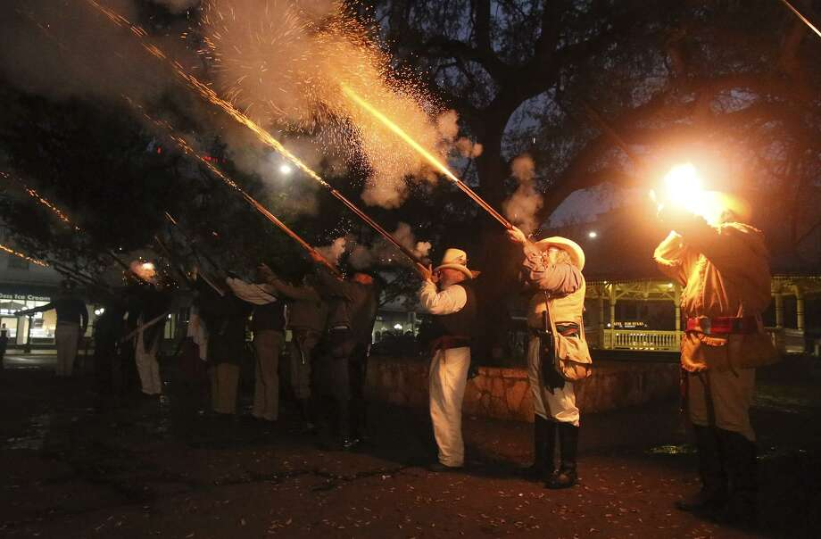 Re-enactors fire muskets near the gazebo at Alamo Plaza as part of ceremonies marking the anniversary. Photo: John Davenport /San Antonio Express-News / ©San Antonio Express-News/John Davenport