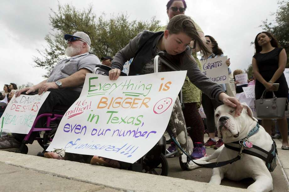 Michael Lummus, left, sits next to Caitriona Cream as pets her service dog Olaf with her mother Nicole Cream, of Round Rock, while attending the Cover Texas Now! rally at the State Capitol in Austin, Monday, March. 6, 2017. The event was to show support for the Affordable Care Act and convince elected officials healthcare is a right for everyone. (Stephen Spillman for Express-News) Photo: Stephen Spillman / Stephen Spillman / stephenspillman@me.com Stephen Spillman