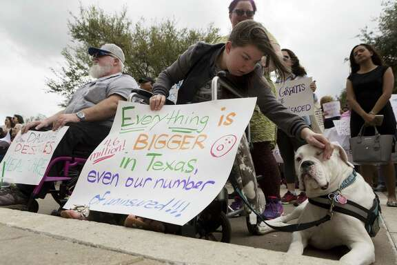 Michael Lummus, left, sits next to Caitriona Cream as pets her service dog Olaf with her mother Nicole Cream, of Round Rock, while attending the Cover Texas Now! rally at the State Capitol in Austin, Monday, March. 6, 2017. The event was to show support for the Affordable Care Act and convince elected officials healthcare is a right for everyone. (Stephen Spillman for Express-News)