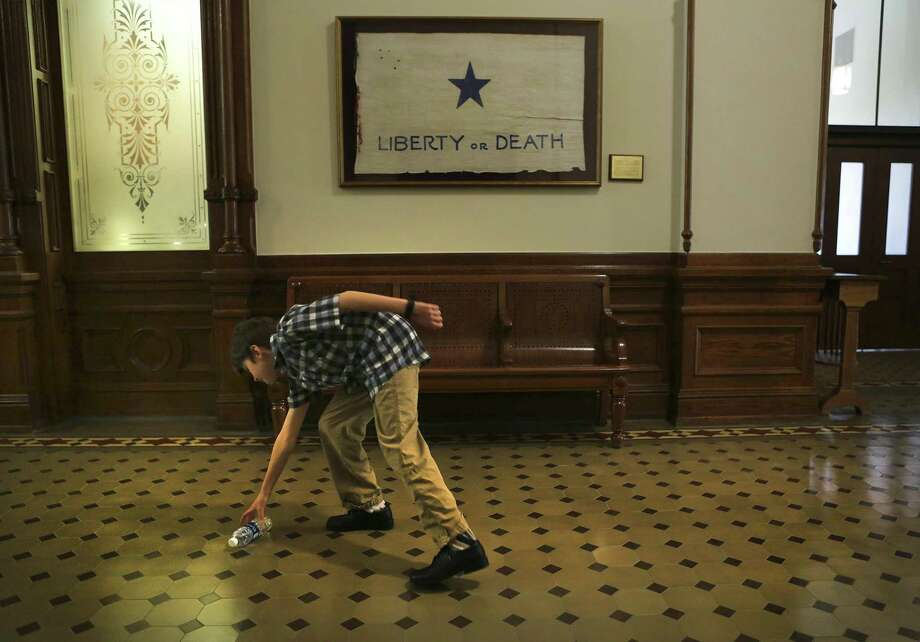 Max Briggle, 9, a transgendered boy picks up his water bottle he dropped in the hallway outside the office of Speaker of the House Joe Straus in the State Capitol during Trans Texas Lobby Day in Austin, TX on Monday, March 6, 2017. Photo: Bob Owen, Staff / San Antonio Express-News / ©2017 San Antonio Express-News