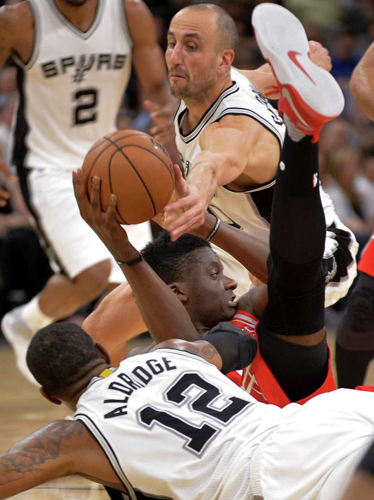 Houston Rockets center Clint Capela, center, of Switzerland, fights for control of the ball against San Antonio Spurs' Manu Ginobili, top, of Argentina, and LaMarcus Aldridge during the first half of an NBA basketball game, Monday, March 6, 2017, in San Antonio. (AP Photo/Darren Abate)