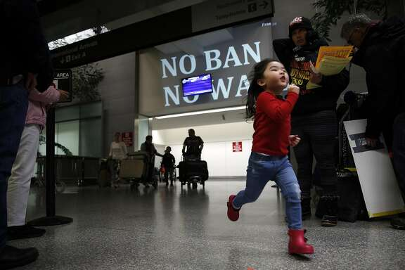 Ella Ronquillo, 3, runs past a protest against President Donald Trump's travel ban after greeting her grandmother who just arrived from the Phillippines at San Francisco International Airport in San Francisco, Calif., on Monday, March 6, 2017.