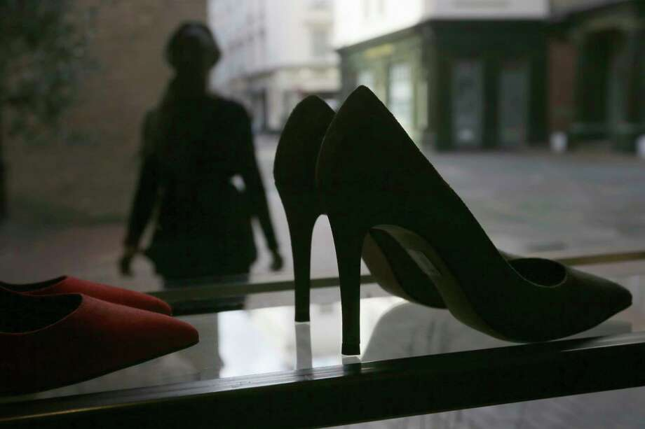 "A person looks at high heels on display at the Pretty Small Shoes store in Bloomsbury, London, Monday, March 6, 2017. Members of Parliament on Monday will debate banning mandatory workplace high heels, in response to a petition by a receptionist who was sent home for wearing flat shoes. The petition, which calls formal workplace dress codes ""outdated and sexist,"" gathered more than 150,000 signatures, making it eligible for a non-binding debate in Parliament. (AP Photo/Tim Ireland) Photo: Tim Ireland, STR / Copyright 2017 The Associated Press. All rights reserved."