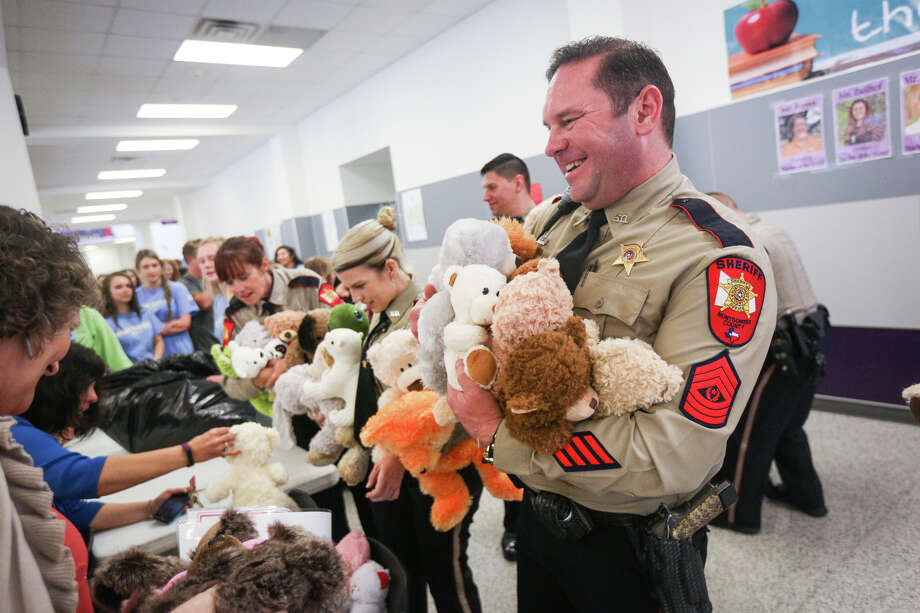 Sgt. Stephen Johnson, Montgomery County Sheriff's Office, gathers a couple armfuls of teddy bears donated by the Montgomery High School's National Honor Society on Monday, March 6, 2017, at Montgomery High School. Photo: Michael Minasi, Staff Photographer / © 2017 Houston Chronicle