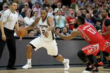 Kawhi Leonard rushes past the Rockets' James Harden on March 6 at the AT&T Center.