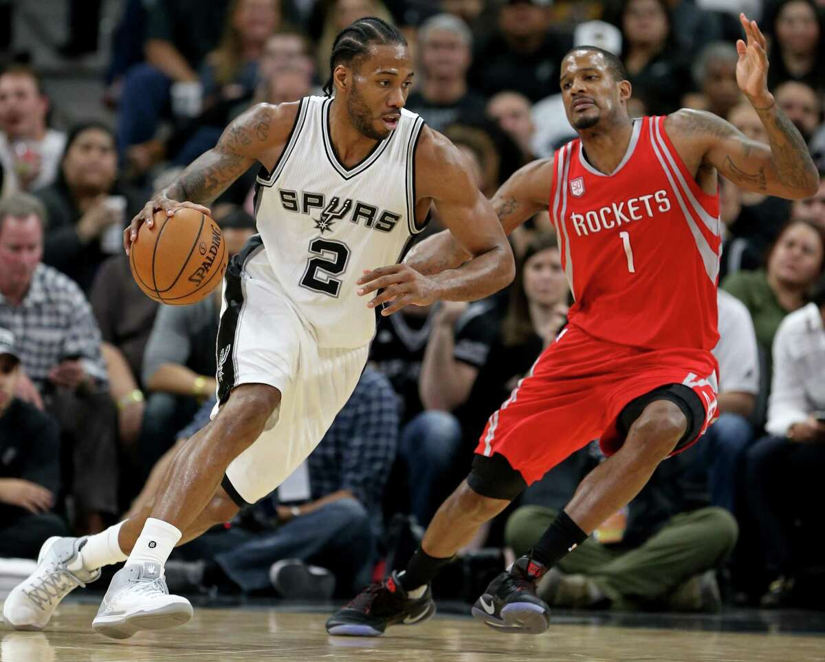 Spurs' Kawhi Leonard looks for room around the Houston Rockets' Trevor Ariza during second half action on March 6, 2017 at the AT&T Center. The Spurs won 112-110.